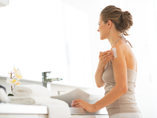 Young woman applying cream on shoulder in bathroom