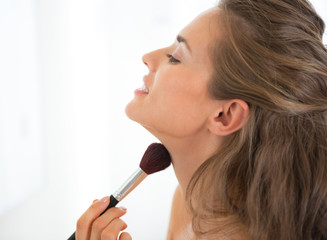 Portrait of young woman applying makeup