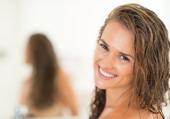 Portrait of smiling young woman with long wet hair in bathroom