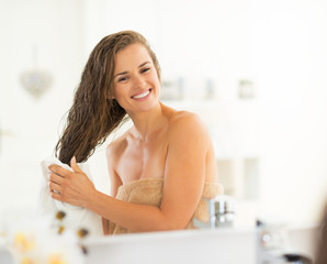 Happy young woman wiping hair with towel