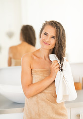 Portrait of happy young woman wiping hair with towel