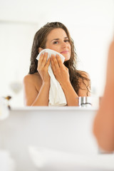 Portrait of young woman wiping with towel in bathroom