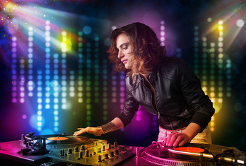 Dj girl playing songs in a disco with light show