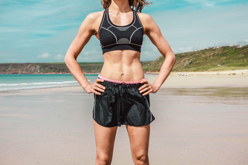 Fit young woman with toned abs on beach