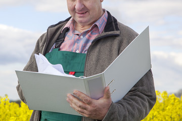 Farmer with file folders in rape field