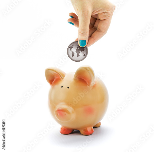 Hand depositing coin with World map in piggy bank
