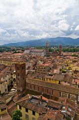 Cityscape of Lucca with cathedral and mountains in back, Tuscany
