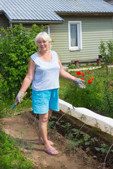 Elderly woman stands in the midst of the garden