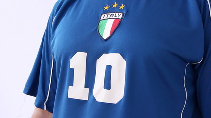 Footballer putting on Italian national outfit