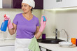 Smiling housewife holding up detergent and soap