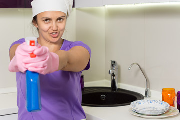 Playful housewife aiming the spray bottle