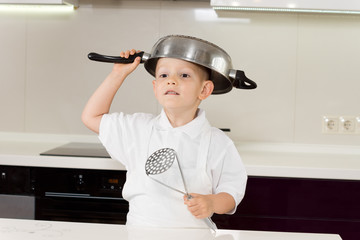 Little boy clowning around with kitchen utensils