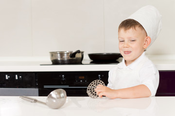 Cute grinning little boy in a chefs hat and apron