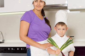 Mother teaching her young son to cook
