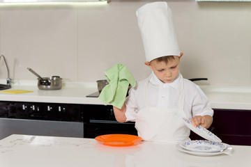 Young boy in chefs uniform washing the dishes