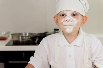 Cute little boy cook with a face full of flour