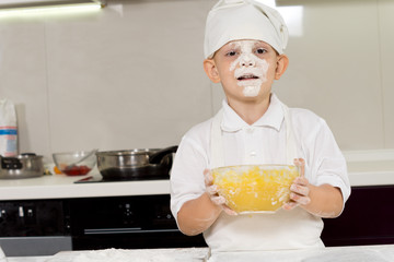 Cute young chef with a face full of flour