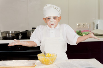 Young cook with a face full of flour shrugging
