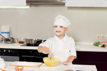 Happy cute young boy baking in the kitchen