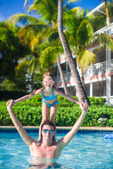Young father and little adorable girl have fun in the pool