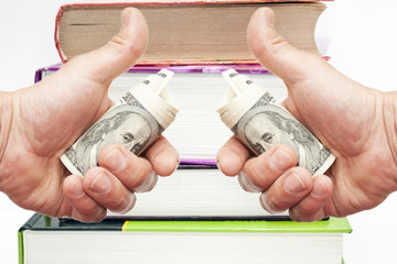Hand with notes of US dollars against books
