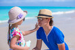 Little girl gets sun cream on her father's nose