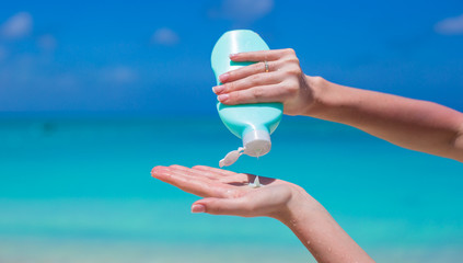 Woman hand putting sunscreen from a suncream bottle