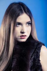 Fashionable girl with long hair. Young woman in fur waistcoat.