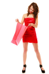 Elegant girl in red dress looking into shopping bag