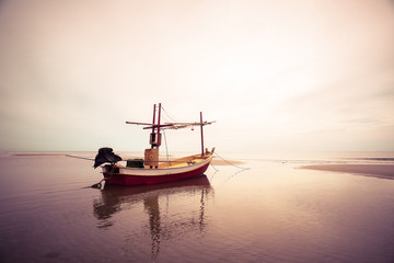 old wooden fishing boat landing on the beach, filter effect colo
