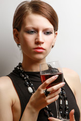 beautiful woman with a wineglass over the wall, isolated on grey