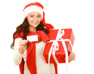 Friendly girl in santa hat with xmas gift showing blank business
