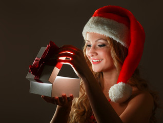 Close-up of smiling woman with gift isolated on black background