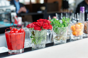 Cocktail cherries, herba and flowers on bar counter