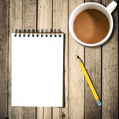 Notebook with pencil, coffee on wooden background