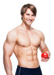 Young smiling bodybuilder holding apple.