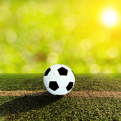 Ball on soccer field and orange sky and sun flare
