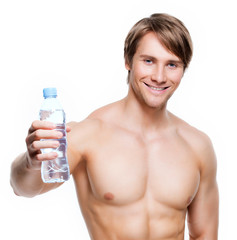 Happy shirtless sportsman holds water.