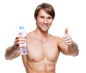 Handsome muscular sportsman holds water.