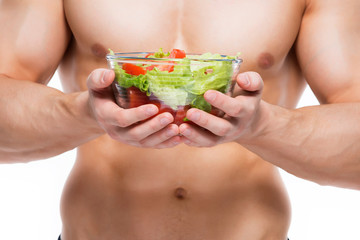 Young man with perfect body holds salad.