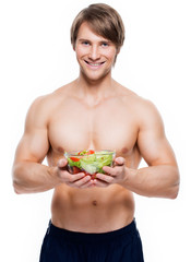 Young muscular man holding a salad.