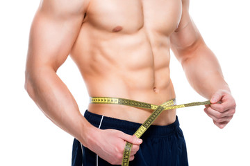 Man with a muscular torso uses measuring tape.