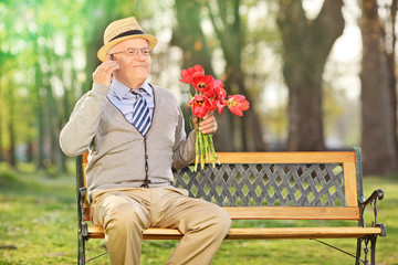 Senior talking on phone and holding red tulips