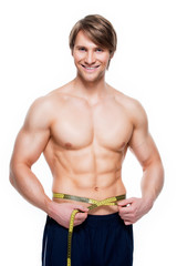 Young man with muscular torso uses measuring tape.