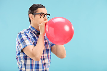 Man with glasses blowing up a balloon