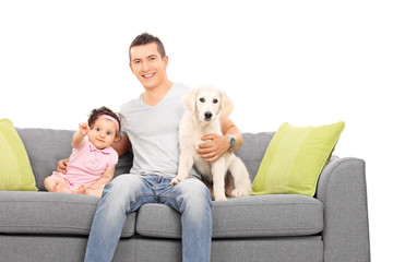 Father posing on couch with daughter and a puppy