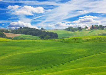 Green hills of Tuscany under  blue sky with white clouds