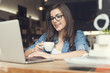 Beautiful hipster woman using laptop at cafe - 65990152