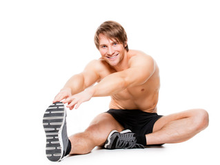 Attractive muscular man stretching on a floor.