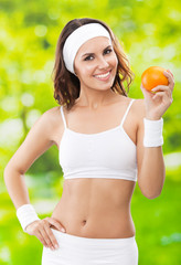 Woman in fitness wear with orange, outdoors